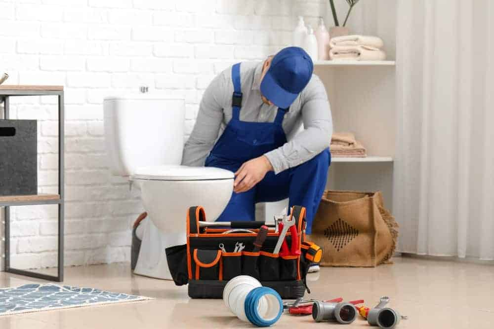 plumber detecting plumbing problems with blue dye tablets